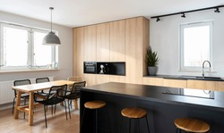 Bright interior of luxurious kitchen with granite kitchen island, stylish chairs and wooden furniture. Dining room in modern apartment with window.
