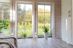 Bright interior, room in wooden house with large window. Scandinavian style.