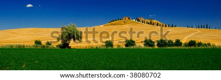 Bright joyful Italian landscape with a green grass, blue sky, white clouds, manor and cypresses.