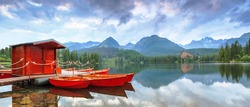 Bright juicy red boats, landing near the bank of the clear blue lake, reflected in the water, with the romantic view on the big green Tatra Mountains
