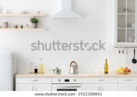 Bright kitchen interior in modern apartment for rent, sale and blogging. Kettle and utensils on white furniture, small refrigerator, shelf with dishes and potted plant in daylight, empty space
