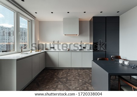 bright kitchen with dark table, convenient location of kitchen accessories and equipment, modern style, White walls, marble working surface and parquet floor. There s a glass of milk on the table and