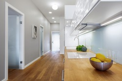 Bright kitchen with wooden floor and countertop next to gray corridor in modern apartment