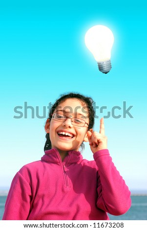 Bright lamp over happy young girl having an idea