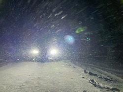 Bright LED headlights of an unrecognizable sportscar illuminates the snowy backcountry road on a freezing cold winter night. Sportscar navigates the idyllic wintry outback during a severe blizzard.