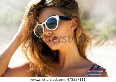 Bright lifestyle fashion portrait of sensual beautiful young woman having fun smiling pretty , natural beauty face,skin care, bright casual trendy sunglasses,bright sexy make up, traveling mood,date