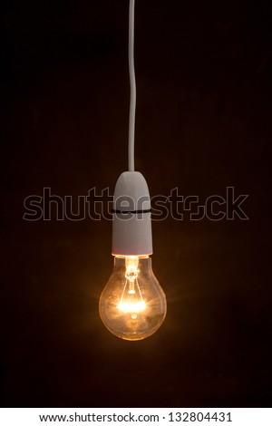 Bright light bulb turned on over black background