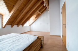 bright light modern simple master bedroom with wooden parquet floors and designer closet and traditional wooden beam bed under slanted ceiling in a refurbished apartment