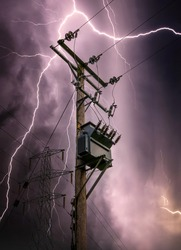 Bright lightning bolts striking electric power pylon tower cables and sub station strike. Electricity discharge cloud to ground storm with transformer on wooden telegraph pole silhouette against sky.