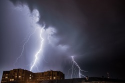 Bright lightning in the black sky over the city