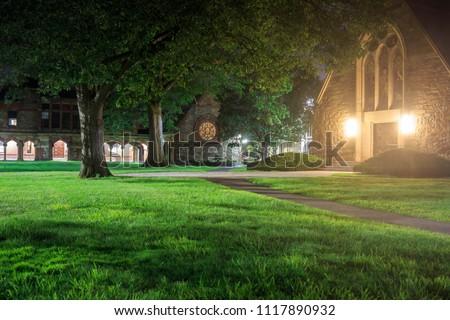 Bright lights from old stone church illuminate green grass at night #1117890932