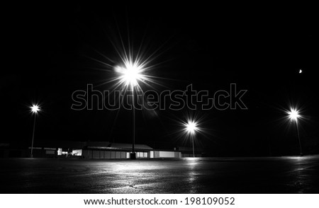 Bright lights in an empty parking lot at night.