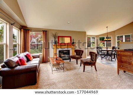 Bright living room with beige carpet floor, leather couch, coffee table and antique style chairs, fireplace and cabinet. Living room open to vaulted ceiling dining area