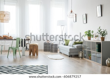 Bright living room with sofa, chair, table and green plants #606879257