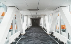 Bright long modern passageway between two towers of an office or a hospital skyscraper with  zig-zag lines of the load-bearing beams, suspended ceiling, heating batteries, and carpeting on the floor