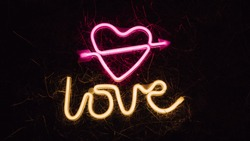 Bright luminous digital neon sign for a store or card beautiful shiny with a love heart pierced by cupid arrow. Glowing amour shape symbol passion in vivid colors. Valentines day concept.