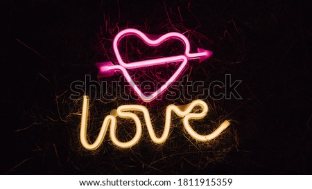 Bright luminous digital neon sign for a store or card beautiful shiny with a love heart pierced by cupid arrow. Glowing amour shape symbol passion in vivid colors. Valentines day concept. Сток-фото ©
