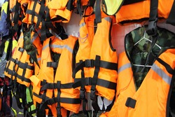 Bright marine life vest signal jackets close up, safety on water tourism activity and watersports