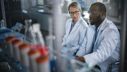 Bright Medical Science Laboratory with Diverse Team of Research Scientists Working. Young Female Microbiologist Talks to a Male Biochemist about New Test Results. High-Tech Equipment.