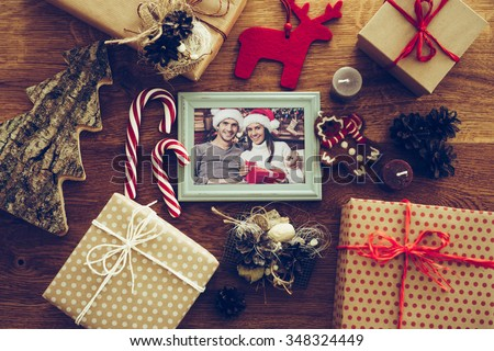 Bright memories. Top view of Christmas decorations and photograph in picture frame laying on the rustic wooden grain