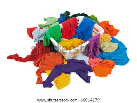 Bright messy clothes in a laundry basket and around it. Isolated on white background.