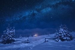 Bright milky way in a night starry sky. Lonely house on a snowy hill with Christmas light.
