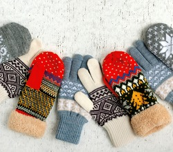 Bright mittens and gloves on a textured background. Gloves and mittens for autumn and winter. Warm knitted clothes for cold seasons. There is space for text.