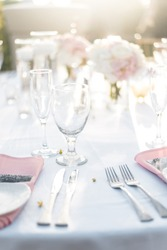 Bright Modern and Elegantly Arranged Wedding Table Setting with Pink and White Roses and Crystal Clear Glasses with Sunset Background at Beautiful Reception in Tropical Island Paradise of Maui Hawaii