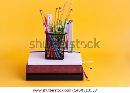 Bright modern minimalistic stationery for schoolwork in a glass for stationery on a stack of notebooks on a yellow background. Back to school concept. With space for copy space
