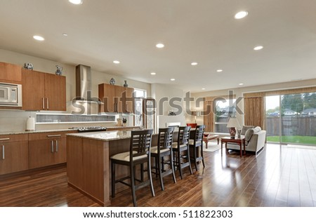 Bright modern open plan kitchen room interior. Large bar style island with stools and polished hardwood floors. Northwest, USA