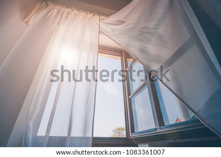 Bright morning sun in the open window through the curtains