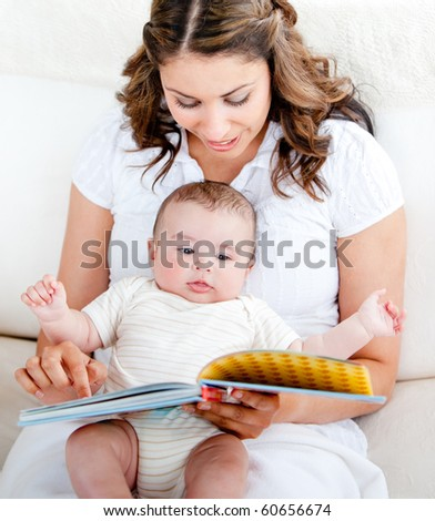 Bright mother showing images in a book to her cute little son at home - stock photo