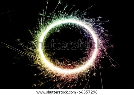 bright multi colored circle of glowing sparks on a black background