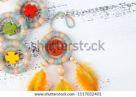 Bright multi colored dream catcher with an orange peace sign and orange yellow feathers close up on a white shabby wooden background. Copy space for text.