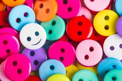 bright multicolored buttons of red, yellow, blue, orange, pink color, among them the white button - smiley stands out among other, top view,  background