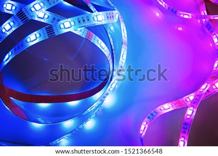 Bright neon LED strip glows blue and pink. Copyspace.