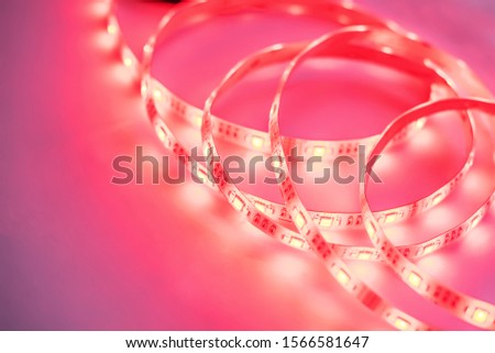 Bright neon LED strip glows coral pink. Copyspace. #1566581647
