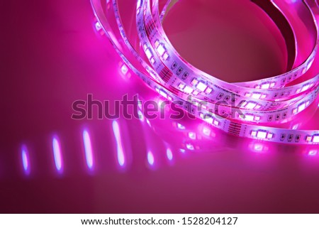 Bright neon LED strip glows pink. Copyspace.
