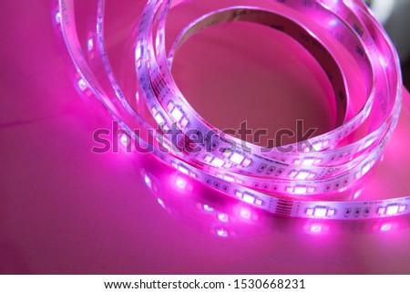 Bright neon LED strip glows pink. Copyspace.