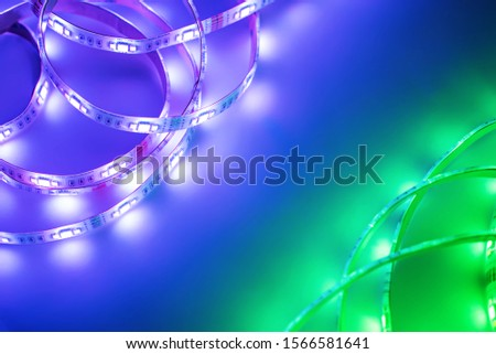 Bright neon LED strip glows purple, violet and green. Copyspace. #1566581641