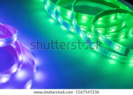 Bright neon LED strip glows purple, violet and green. Copyspace. #1567547236