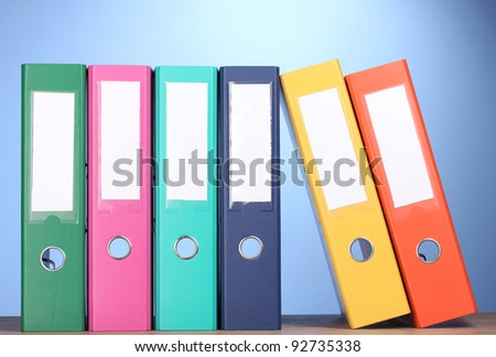 bright office folders on wooden table on blue background