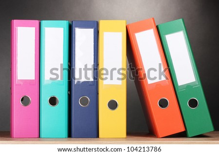 bright office folders on wooden table on grey background
