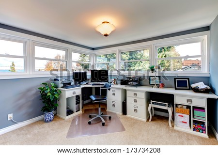 Bright office room with light tones furniture and beige carpet floor