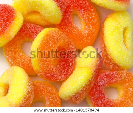 Bright orange and yellow fizzy children's candy sweets in a pile in a sweet / candy shop / store, sugar and sour taste.