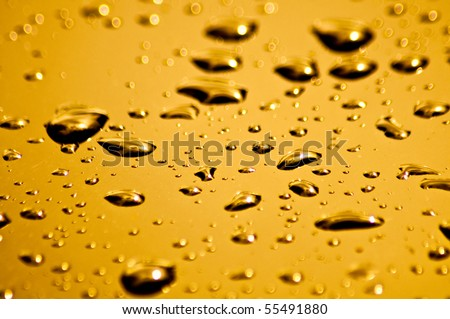 Bright orange and yellow water droplets on the hood of a car