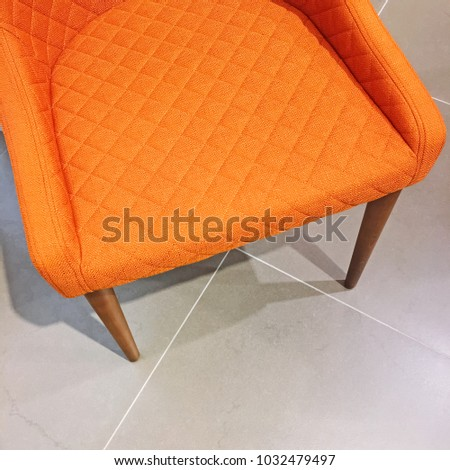 Bright orange armchair on tile floor. Modern style with a retro feel. #1032479497