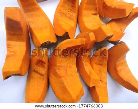 Bright orange colored pieces of fleshy pumpkin shell.  Stock fotó ©
