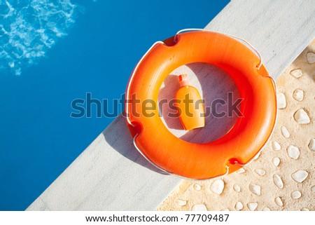 bright orange life preserver floating on the coast swimming pool and sunblock - stock photo