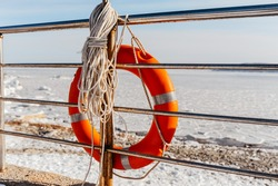 bright orange lifebuoy to help a drowning man, tied with ropes to a metal railing, against the backdrop of a frozen sea in ice